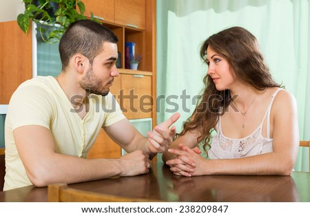 Young married couple having serious talking at the table in home - stock photo
