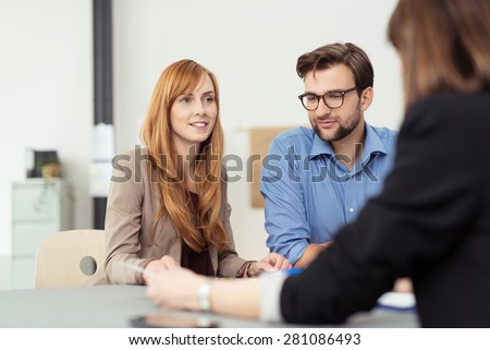Young married couple in a meeting with a broker or agent with focus to the attractive redhead wife - stock photo