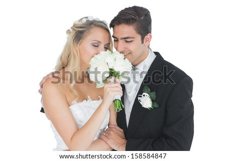 Young married couple posing having a sniff of the bouquet on white background - stock photo