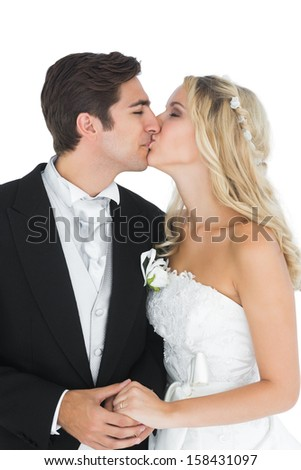 Young married couple posing kissing each other while holding hands  - stock photo