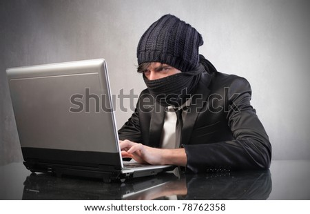 Young masked hacker using a laptop - stock photo