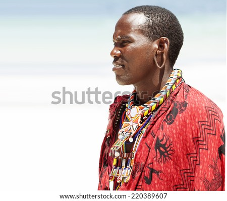 Young massai man posing on bright sunny beach in Kenya. - stock photo