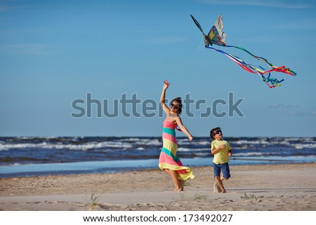 Young mather and her son playing with kite - stock photo