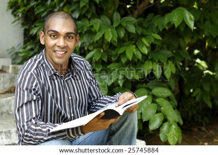 Young Mauritian, Indian & African looking man reading a book outdoors - stock photo