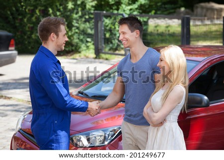 Young mechanic handshaking with couple by car - stock photo