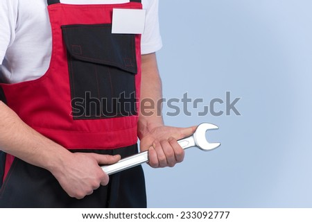 Young mechanic in red and black overall standing against blue background. cropped picture of man holding spanner - stock photo