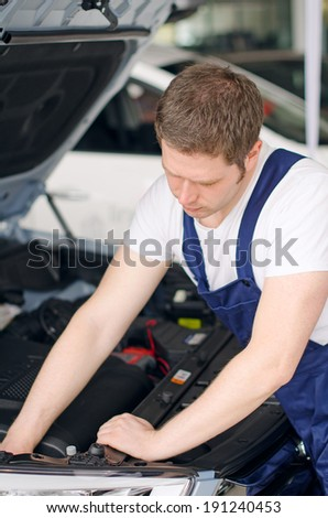 Young mechanic repairing car in service center - stock photo