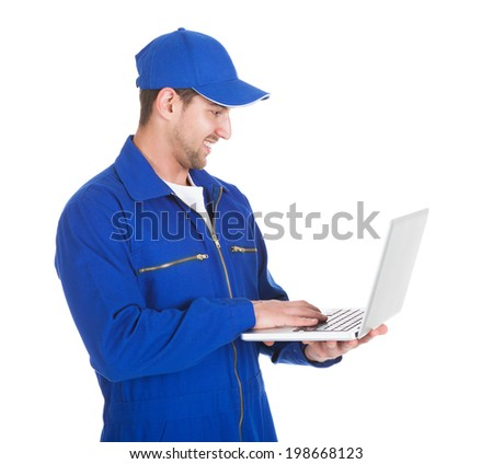 Young mechanic using laptop over white background - stock photo