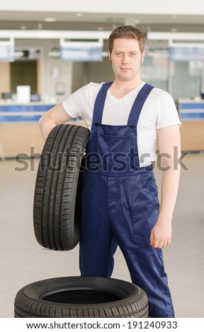 Young mechanic with tire in service center. - stock photo