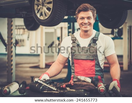 Young mechanic with tools in a car workshop - stock photo