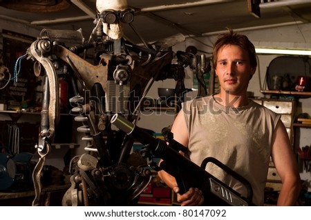 Young mechanic worker finished his robot - stock photo