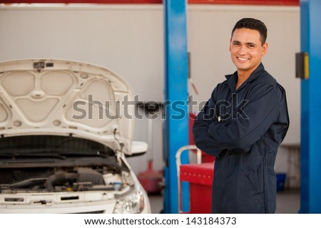 Young mechanic working at an auto shop and smiling - stock photo