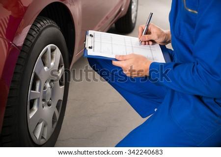 Young Mechanic Writing On Clipboard White Examining Car Wheel - stock photo