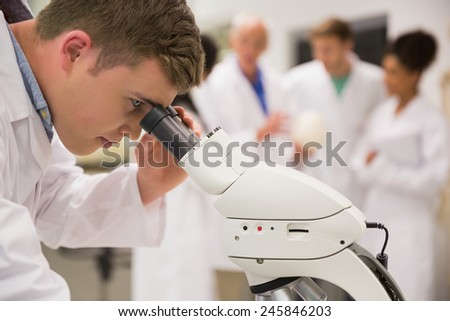 Young medical student working with microscope at the university - stock photo