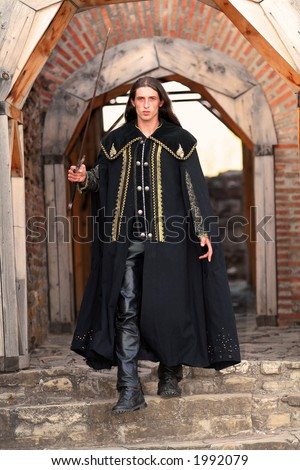 Young medieval blade-smith sword-cutler prince with black mantle like highlander - stock photo