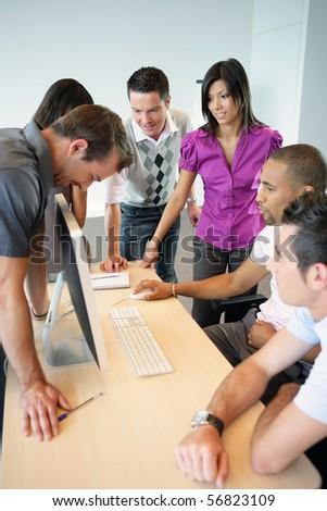 Young men and young women standing in front of a desktop computer - stock photo