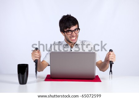 Young men at dinner table eating technology with a funny face expression - stock photo