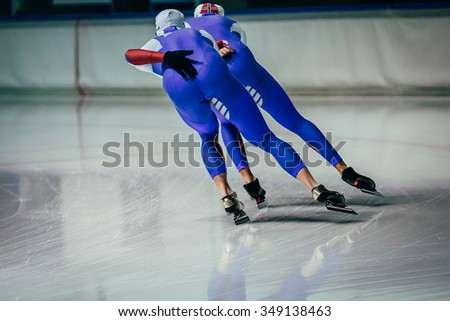 young men athletes skater equally roll during warm-up before competitions in speed skating - stock photo