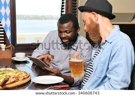 Young men drinking beer and talking in cafe - stock photo