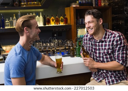 Young men drinking beer together at the bar - stock photo