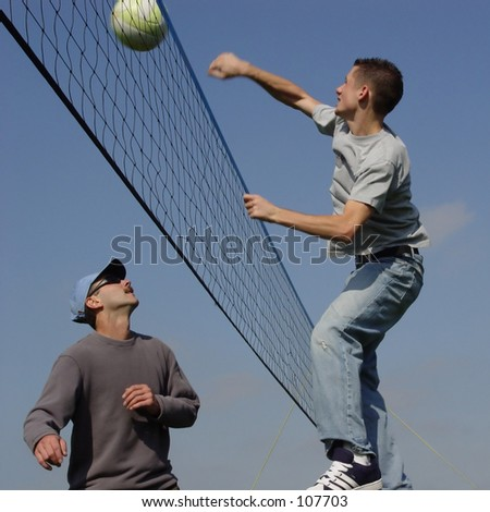 Young men hitting the ball over the net - stock photo