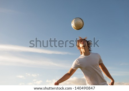 Young men hitting the soccer ball - stock photo