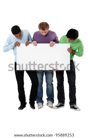 Young men holding up a blank sign - stock photo