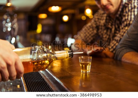 Young men in casual clothes is sitting at bar counter in pub, a bartender is pouring alcoholic beverage into glass, close-up - stock photo