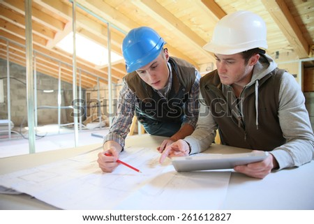 Young men in professional training working on building site - stock photo