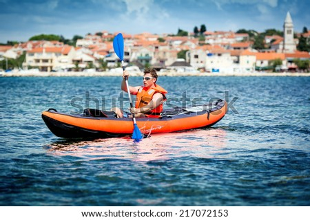 Young men paddle a kayak on the sea - stock photo