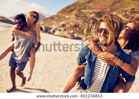 Young men piggybacking women on the sea shore. Mixed race young people enjoying summer vacation at beach. - stock photo