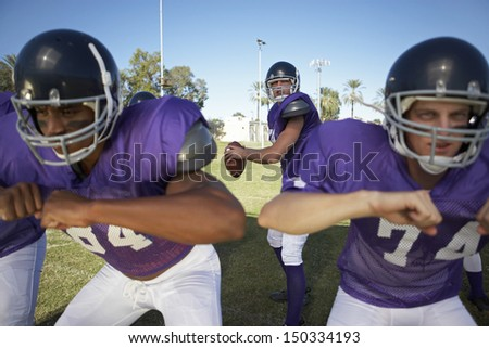 Young men playing American football on field - stock photo