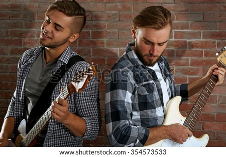 Young men playing guitars on brick wall background - stock photo