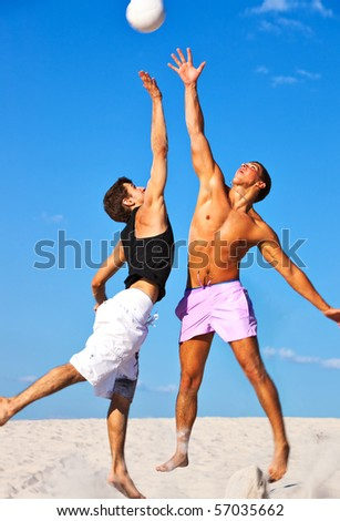 Young men playing volleyball on beach. - stock photo