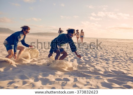 Young men running race on the beach. Group of young people playing games on sandy beach on a summer day. - stock photo