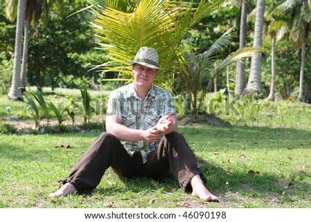 Young men sittin under palm - stock photo