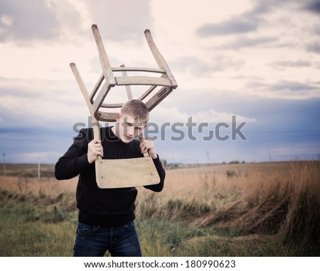 young men with old chair outdoor - stock photo