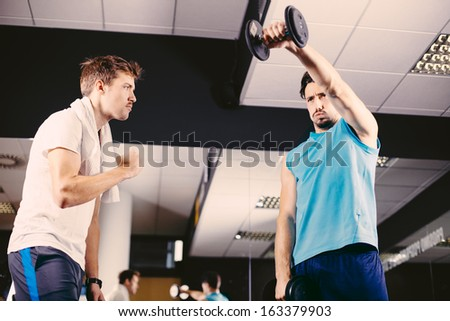 Young men working out in gym or health club - stock photo