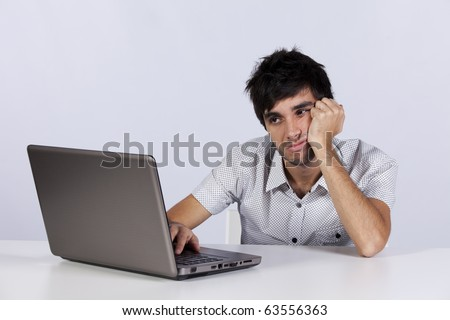 Young men working with his laptop with a bored face - stock photo