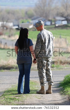 Young military man and young woman holding hands and saying goodbye. - stock photo