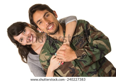 young military soldier returns to meet his wife girlfriend hugging isolated on white - stock photo