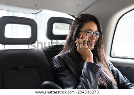 Young mixed race businesswoman portrait inside a taxi in Canary Wharf area in London talking at the phone. - stock photo