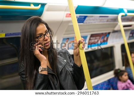Young mixed race businesswoman portrait inside underground wagon in London talking at the phone. - stock photo