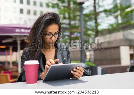 Young mixed race businesswoman portrait outdoors in Canary Wharf area in London working with tablet and drinking a coffee. - stock photo