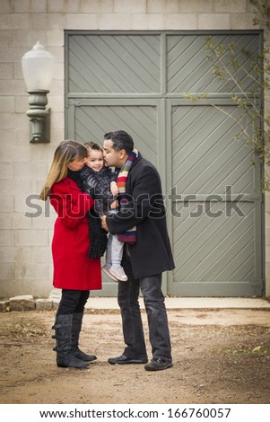 Young Mixed Race Couple in Winter Clothing Hugging and Kissing Son in Front of Rustic Building Together. - stock photo