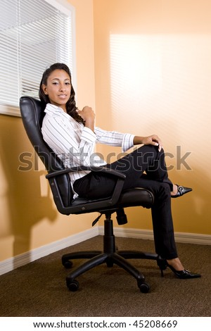 Young mixed-race Hispanic African-American female office worker sitting in chair - stock photo