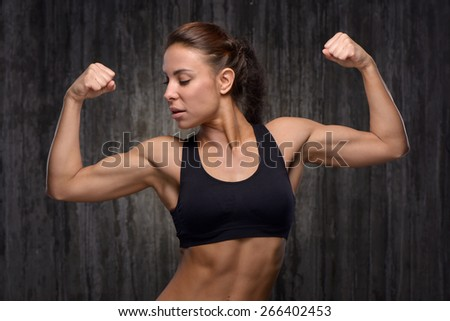 Young mixed race sporty woman wearing black tracksuit for training. She demonstrating her biceps. Fitness concept - stock photo