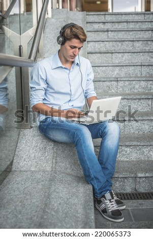 young model handsome blonde man with notebook smartphone and headphones in the city - stock photo