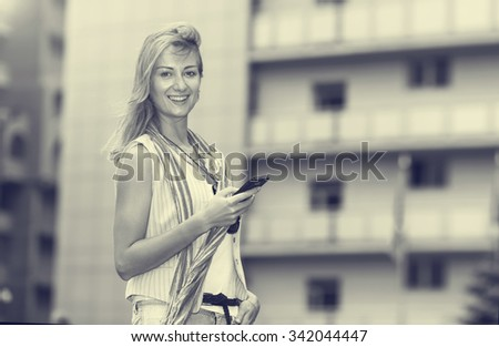 Young modern beautiful hipster woman using smart phone in the city. Fashionable young woman busy with her mobile phone while walking on city street. Black and white sepia toned image. - stock photo