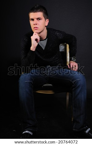 Young modern black haired man  sitting in the dark and thinking - stock photo